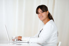 Charming woman looking at you working on laptop Royalty Free Stock Image