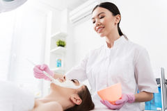 Charming woman is lying while beautician employing anti-aging agent Stock Image