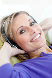 Charming woman lying down on sofa listening music