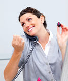 Charming woman on phone painting her nails Stock Image