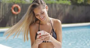 Charming woman with phone in pool Stock Images