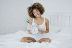 Charming woman posing on bed with clock Stock Photos