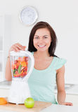 Charming woman posing with a blender Stock Photo
