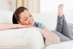 Charming woman posing while lying on a sofa Stock Images