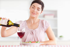 Charming Woman pouring redwine in a glass. In a kitchen Royalty Free Stock Photography