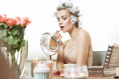 Charming woman putting on a makeup Stock Photos
