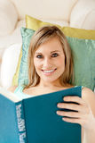 Charming woman reading a book lying on a sofa Royalty Free Stock Images