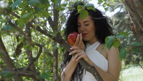 Charming woman with red apple enjoy a smell of fruit and smiles to camera. Beautiful woman in dress holds red apple in hands and posing for camera. Charming stock video