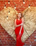Charming woman in red dress on golden heart in studio. Charming elegant woman in a red dress on a background of a golden heart in the studio Royalty Free Stock Photos