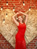 Charming woman in red dress on golden heart in studio. Charming elegant woman in a red dress on a background of a golden heart in the studio Royalty Free Stock Images