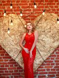 Charming woman in red dress on golden heart in studio. Charming elegant woman in a red dress on a background of a golden heart in the studio Royalty Free Stock Photo
