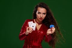 Beautiful curly woman in a glittered dress, holding some playing cards and gambling chips. Casino. Charming woman in a red sparkly dress and exquisite jewelry royalty free stock image