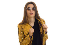 Charming woman in round sunglasses and bright golden jacket. Isolated on white background royalty free stock photo