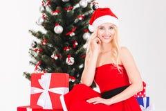 Charming woman in santa claus hat sitting near Christmas tree Royalty Free Stock Photos