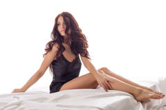 Charming woman sits with her feet dangling off bed Royalty Free Stock Image