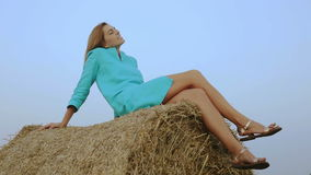 Charming woman sitting on a haystack on blue sky background. stock footage