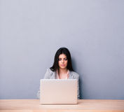 Charming woman sitting at the table with laptop Royalty Free Stock Photos
