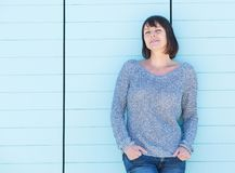 Charming woman standing against blue background Stock Photography