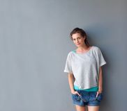 Charming woman standing against gray background in shorts Stock Photo