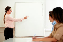 Charming woman standing and pointing at whiteboard Royalty Free Stock Images