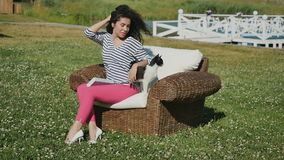 Charming woman strokes a cat sitting in wicker armchair on green lawn stock footage