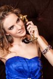 A charming woman with stylish curly hairstyle wearing a blue dress talking on vintage old phone in retro style. Portrait of a charming woman with stylish curly stock photos