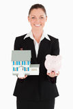 Charming woman in suit holding business objects Stock Photography