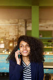 Charming woman talking on mobile phone call in cafe Stock Photos