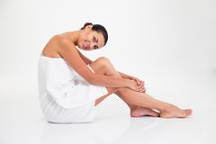Charming woman in towel sitting on the floor Stock Images