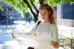 Charming woman traveler studying atlas before strolling outdoors during unforgettable journey Stock Images