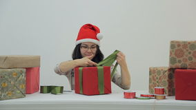 Charming woman is tying ribbon on holiday gift. Fun and wonderful brunette in red New Year cap trimmed with white fur, black square glasses and gray sweater stock video footage