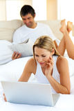 Charming woman using a laptop lying on bed Royalty Free Stock Photos