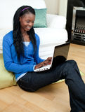 Charming woman using a laptop sitting on the floor Stock Photography