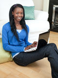 Charming woman using a laptop sitting on the floor Royalty Free Stock Photography