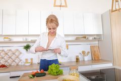Culinary girl holds smartphone in hands and takes photo of veget. Charming woman using mobile gadget records video of cooking process and photographs composition Stock Image