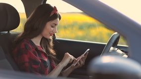 Charming woman using smartphone while driving car stock video