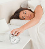 Charming woman waking turning off alarm clock Royalty Free Stock Image