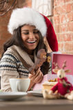 Charming woman wearing Santa Claus hat opening Christmas gift. In a restaurant Stock Image