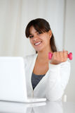 Charming woman with weights in front of laptop Stock Photography