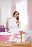 Charming woman in white bathrobe relazing on beauty salon decor Stock Images