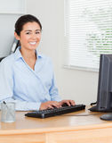 Charming woman working on a computer while sitting Stock Photography
