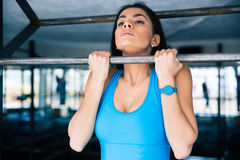 Charming woman working out on horizontal bar. At gym Royalty Free Stock Image
