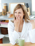 Charming woman yawning while drinking coffee Stock Images