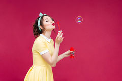 Charming woman in yellow dress standing and blowing soap bubbles Stock Photos