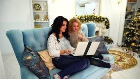 Charming women communicate with parents on Internet through laptop, sitting on couch in bright living room with festive stock video