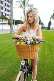Charming women cyclist enjoying rest after riding on vintage bike in beautiful park Stock Photo