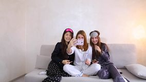 Funny girls doing selfie at home party, smiles on their faces and sitting on sofa background of light wall in room. Charming women in good spirits doing selfie stock video footage