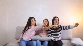 Funny girls listen to music and dance, smiles on their faces and sitting on sofa background of light wall in room. stock video footage