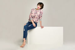 Charming women in jacket with flowers and blue jeans with holes. Royalty Free Stock Images
