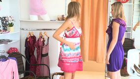 Charming women trying dresses together stock video